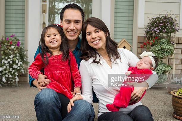 Cute young ethnic family Christmas picture in front of home