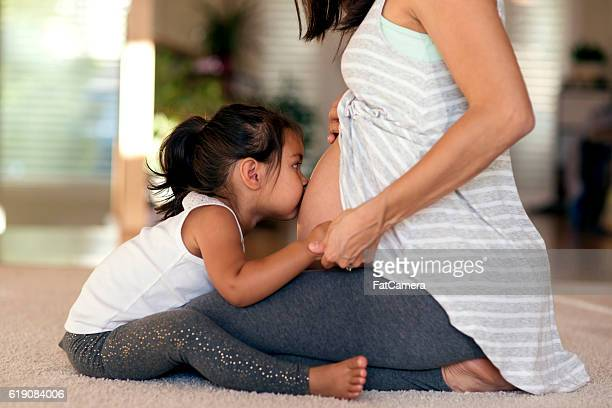 Cute young ethnic girl kissing mommys pregnant belly