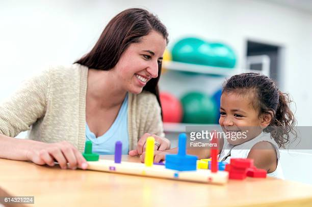 Cute young ethnic girl smiling with her physical therapist