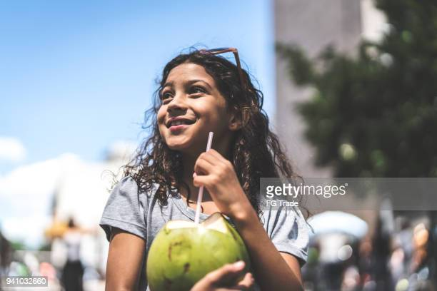 cute young girl drinking coconut water on a city break - coconut water stock pictures, royalty-free photos & images