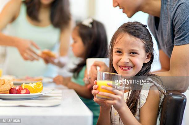 Cute young girl drinking orange juice and smiling