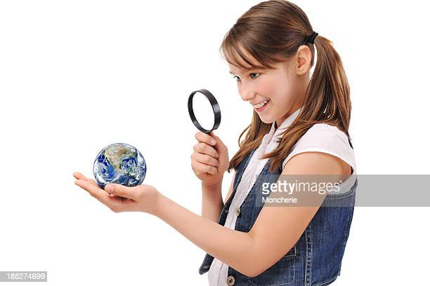 Cute Young Girl Examining The Earth