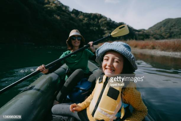 cute young girl having a good time on kayak with mother - 栃木県 ストックフォトと画像