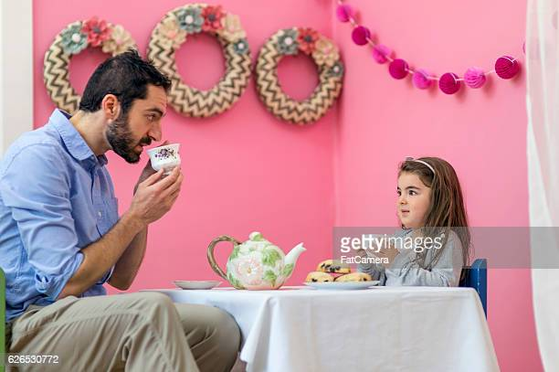Cute young girl having a tea party with her dad