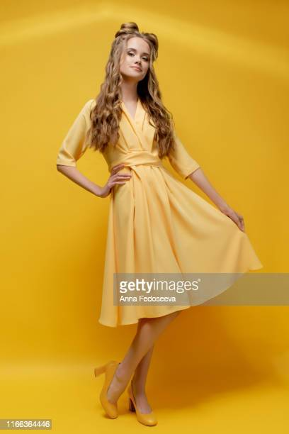 a cute young girl in a yellow dress, in shoes with heels on a yellow background with a haircut and curly long hair. yellow fashionable, stylish, youth clothing. salon hairstyles and makeup. - long bright yellow dress stock pictures, royalty-free photos & images