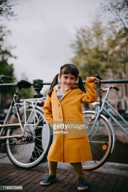 cute young girl in yellow coat dancing on street, amsterdam - alternative pose stock pictures, royalty-free photos & images