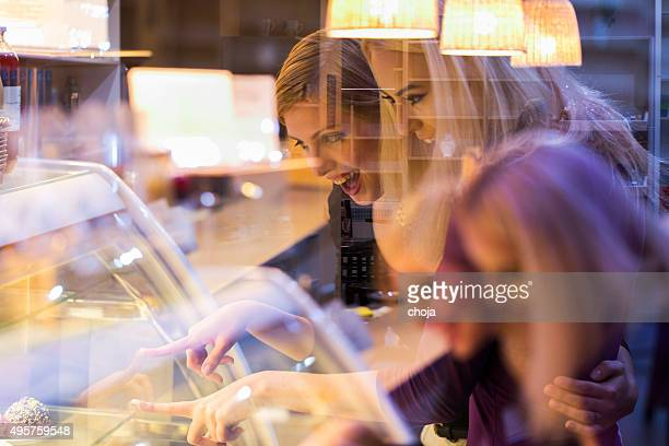 Cute young girl looking at display window with cakes