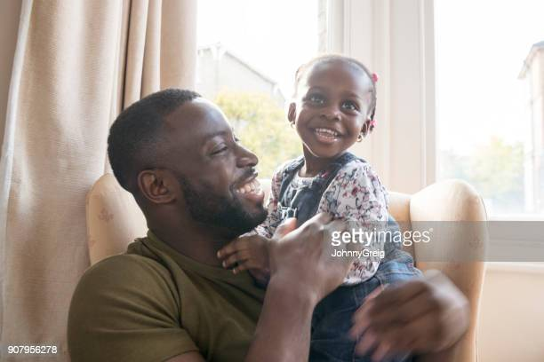 cute young girl on father's lap smiling and looking away - daughter photos stock photos and pictures