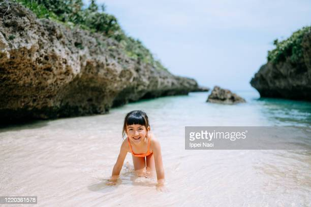 cute young girl playing in tropical beach water, okinawa, japan - ippei naoi stock pictures, royalty-free photos & images