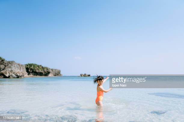 cute young girl playing in tropical water at beach, okinawa, japan - ippei naoi stock pictures, royalty-free photos & images