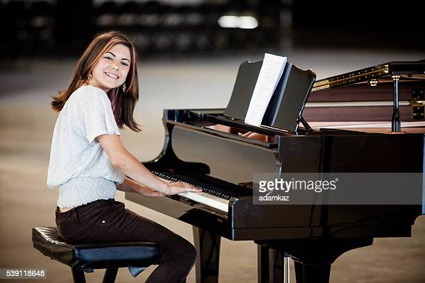 cute young girl playing piano - grand piano stock photos and pictures