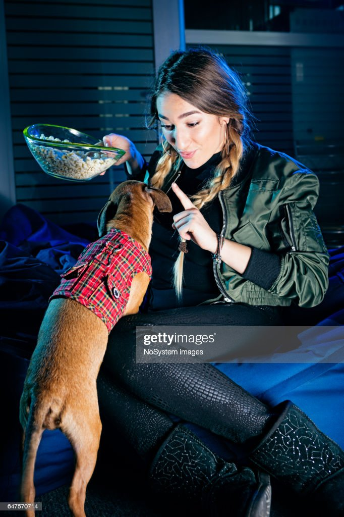 Cute young girl, playing with her puppy, eating popcorn, indoors : Stock Photo