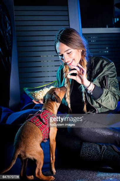 cute young girl, playing with her puppy, eating popcorn, indoors - dog eats out girl stock photos and pictures