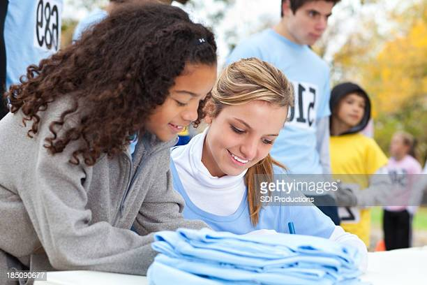 Cute young girl signing up at an outdoor charity race