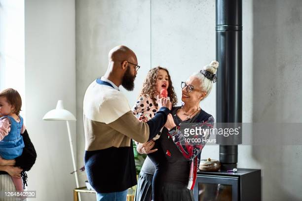 cute young girl singing into microphone with father and grandma - daughter stock pictures, royalty-free photos & images