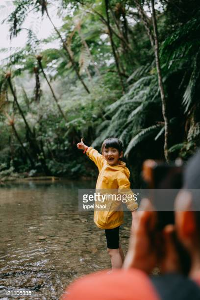 cute young girl smiling at camera in forest river - reality fernsehen stock pictures, royalty-free photos & images