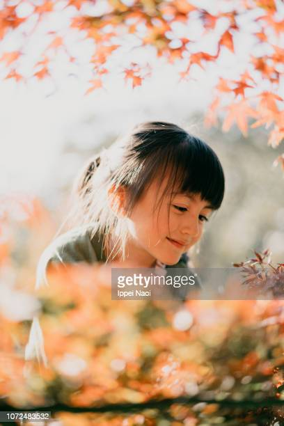 Cute young girl smiling enjoying Autumn color leaves