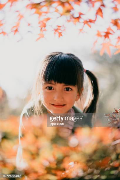 Cute young girl smiling enjoying autumn colour leaves