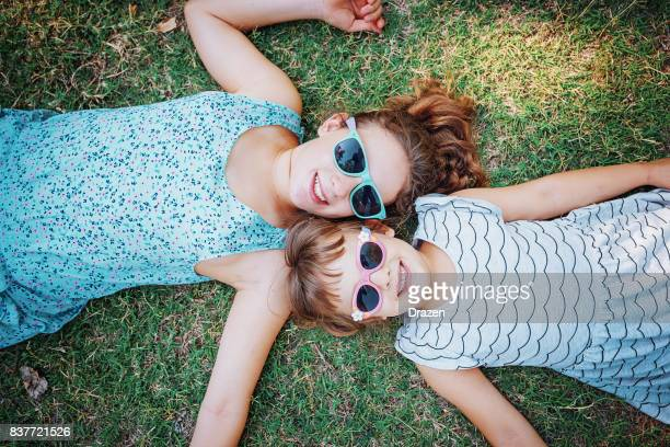 Cute young girls lying on the grass in nature and making faces