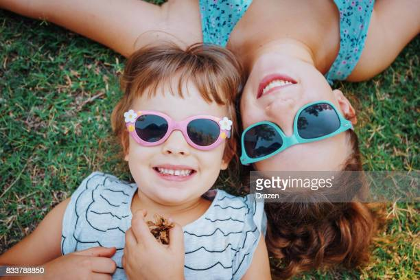 Cute young girls lying on the grass in park and smiling