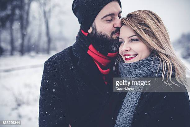 Cute young hipster couple having fun in winter