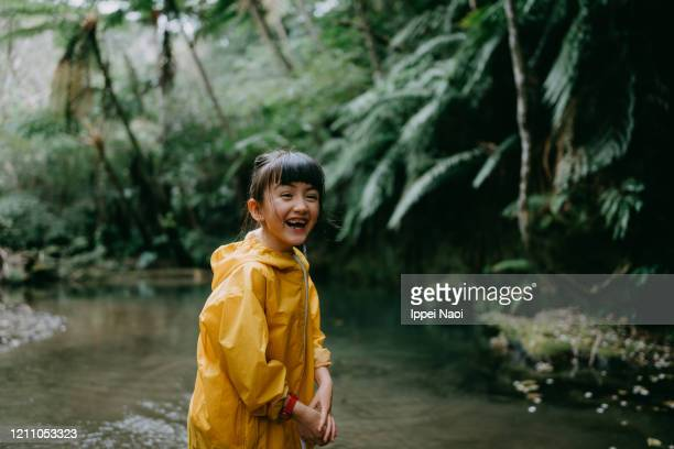 cute young mixed race girl laughing in rainforest, okinawa, japan - reality fernsehen stock pictures, royalty-free photos & images