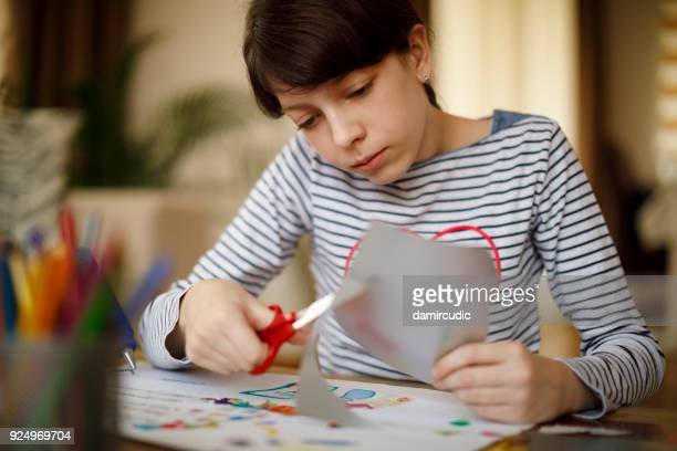 Cute young teenage girl doing homework project