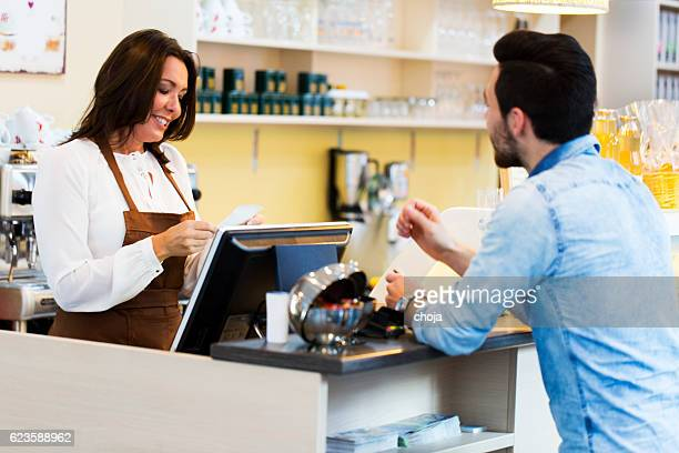 Cute young waitress  by the cash register making bill