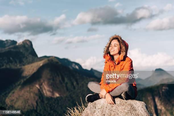 leuke jonge vrouw genieten van het buitenleven op de berg - hoofddeksel stockfoto's en -beelden