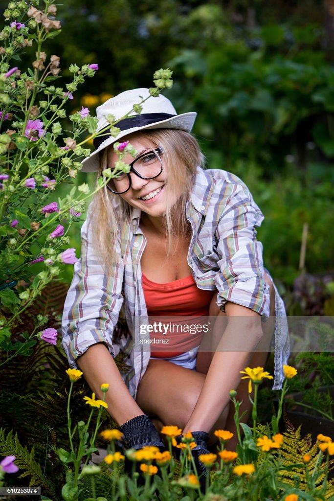 Cute young woman gardener among the flowers : Foto de stock
