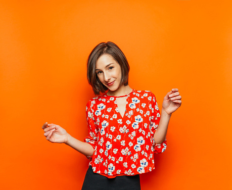 Cute young woman on orange background - gettyimageskorea