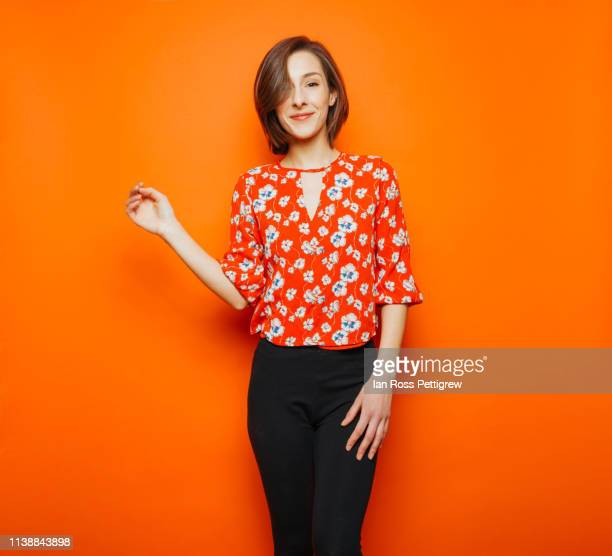 cute young woman on orange background - orange farbe stock-fotos und bilder