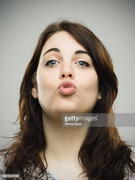 Cute young woman puckering against gray background