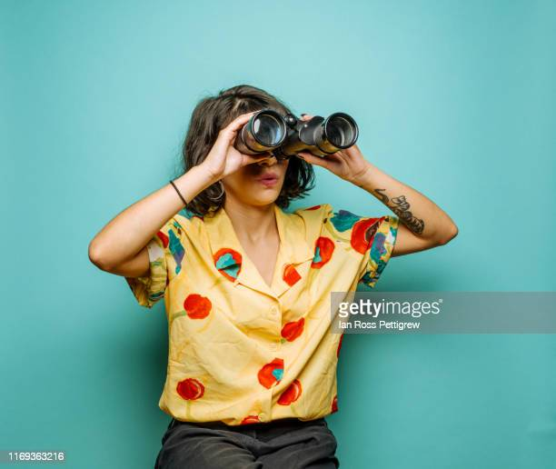 cute young woman using binoculars - binoculars stock pictures, royalty-free photos & images