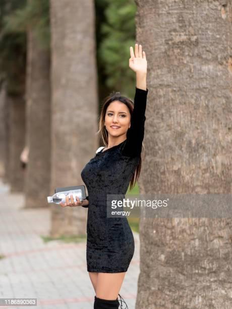 cute young woman waving hand - bella ciao foto e immagini stock