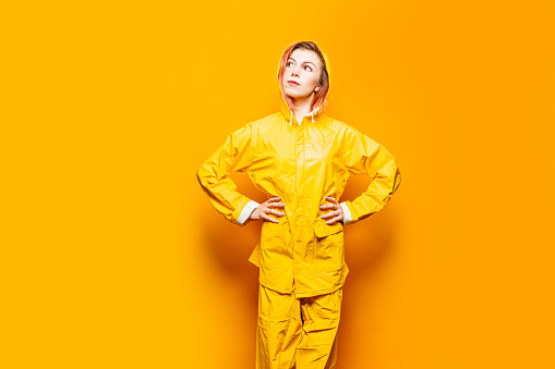 Cute young woman wearing yellow raincoat and pants - gettyimageskorea
