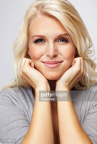 Hübsche Junge Frau mit Händen am Kinn