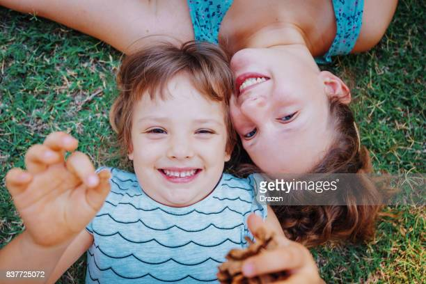Cutesisters lying on the grass in park and smiling