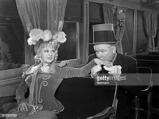 Cuthbert J. Twillie plants a kiss on the hand of Flower Belle Lee in a scene from iMy Little Chickadee/i .