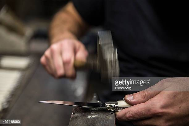 A cutler hammers a rivet into a pocket knife bolster at Forge De Laguiole traditional knife and cutlery factory in Laguiole France on Monday Nov 2...