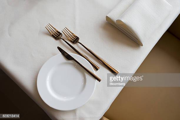 Cutlery and napkins sit on a restaurant table in the First Class passenger lounge at Munich Airport's Terminal 2 during the official opening ceremony...