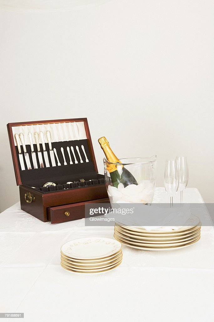 Cutlery box with a champagne bottle and tableware on a dining table : Stock Photo