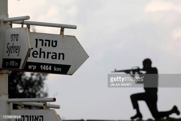 Cutout of an Israeli soldier is seen behind signs pointing out distances to different cities at an army post in Mount Bental in the Israeli-annexed...