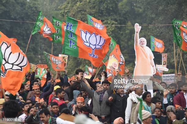 Cutout of India's Prime Minister Narendra Modi is held up as supporters of the Bharatiya Janata Party listen to his speech during a rally in New...