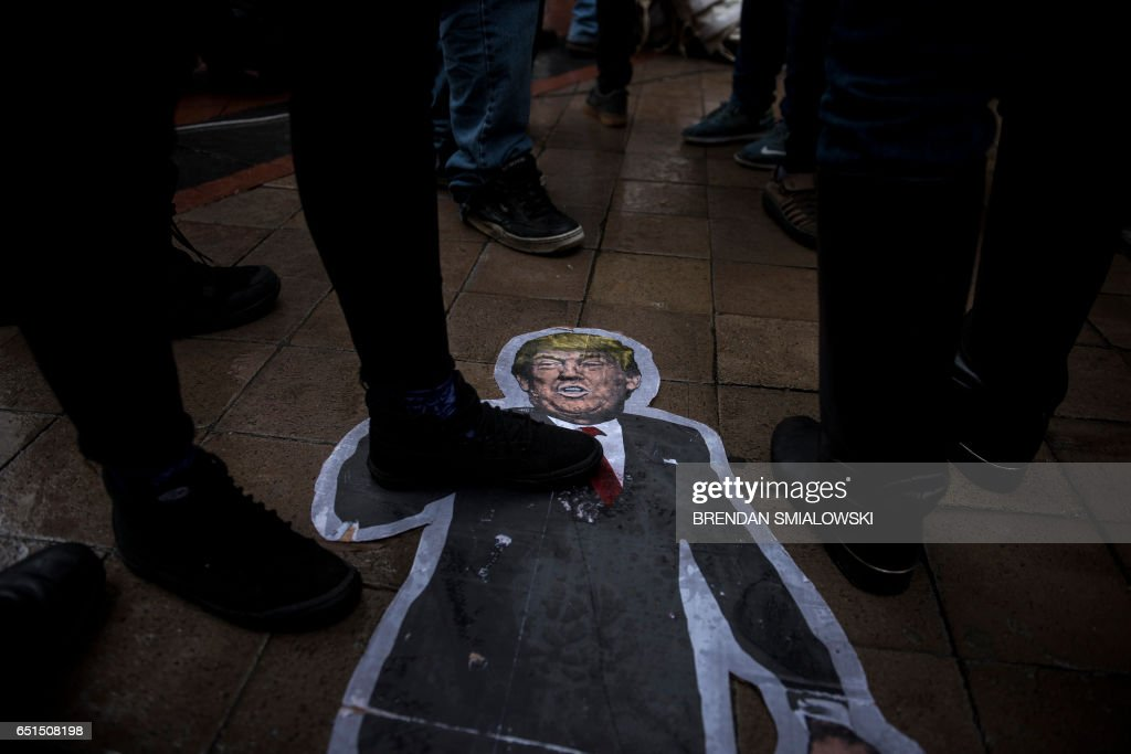 A cutout of US President Donald Trump is seen on the ground as activists rally in front of the Trump International Hotel to protest the Dakota Pipeline and rally for Native American rights march during the Native Nations Rise protest on March 10, 2017 in Washington, DC. Native tribes from around the US gathered for four days of protest against the administration of US President Donald Trump and the Dakota Access oil pipeline. / AFP PHOTO / Brendan Smialowski