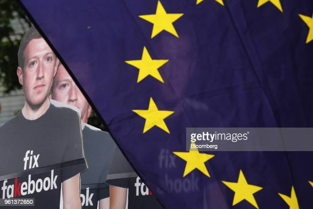 Cutouts of Facebook Inc. Chief Executive Officer Mark Zuckerberg stand beside a European Union flag during a protest outside the Berlaymont building...