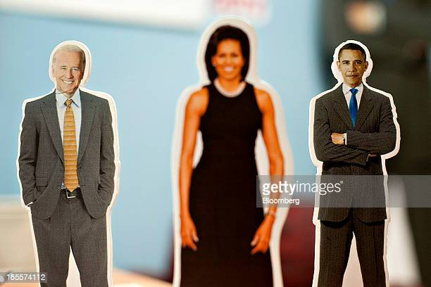 Cutouts of US President Barack Obama right Vice President Joe Biden left and first lady Michelle Obama stand on a desk while volunteers call...