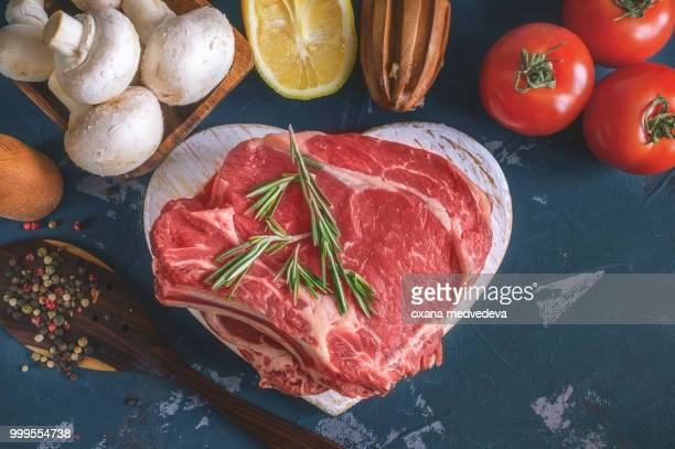 Cuts of beef for grilling on a wooden cutting Board with the Bay leaf, rosemary, olive oil and...