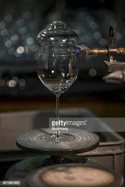 A cutter scores the outside of a wine glass to allow removal of the pipecap during the cracking process at the Novosad Son Glassworks in Harrachov...