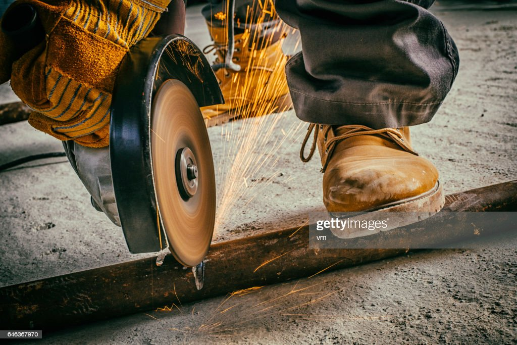 Cutting a metal rod with a circular saw : Stock Photo